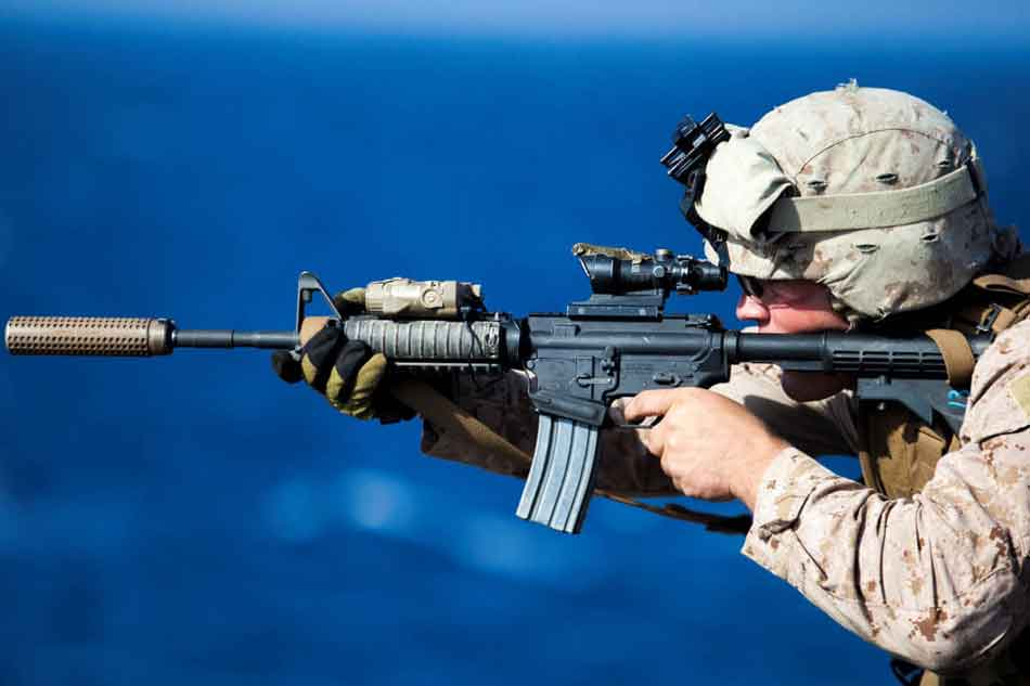 a soldier firing an ar15 sighting through an optic sight