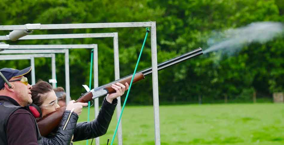 a woman aiming at a clay pigeon shooting