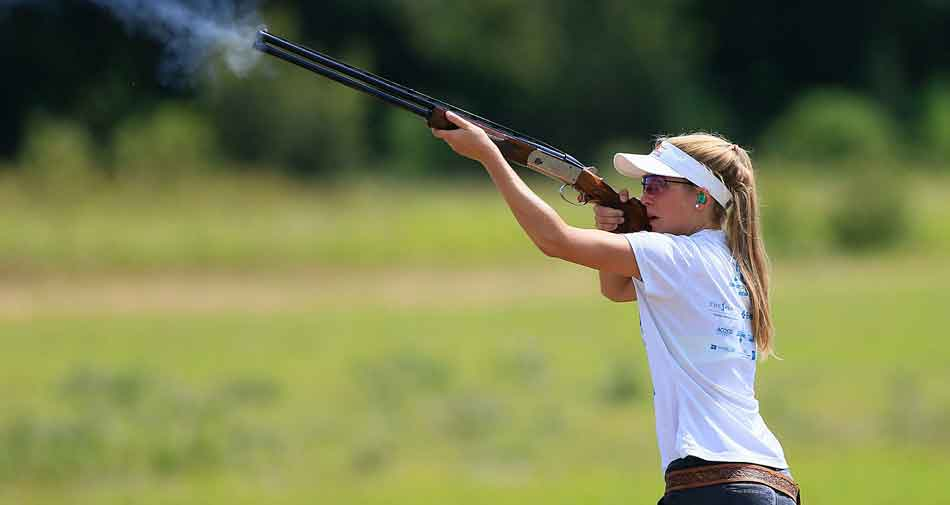 a woman aiming at a clay pigeon