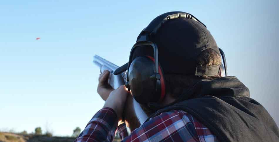 a man aiming at a clay pigeon