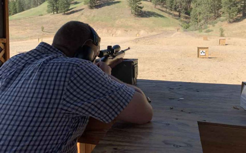 A man on a rifle range target shooting