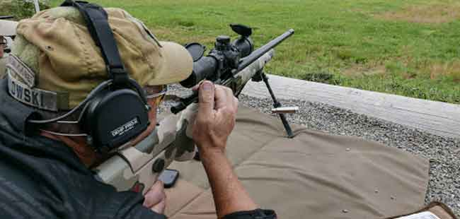 a guy shooting a rifle