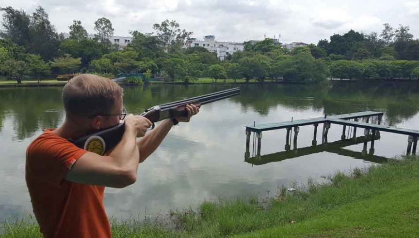 a man clay sport shooting with a shotgun over a lake