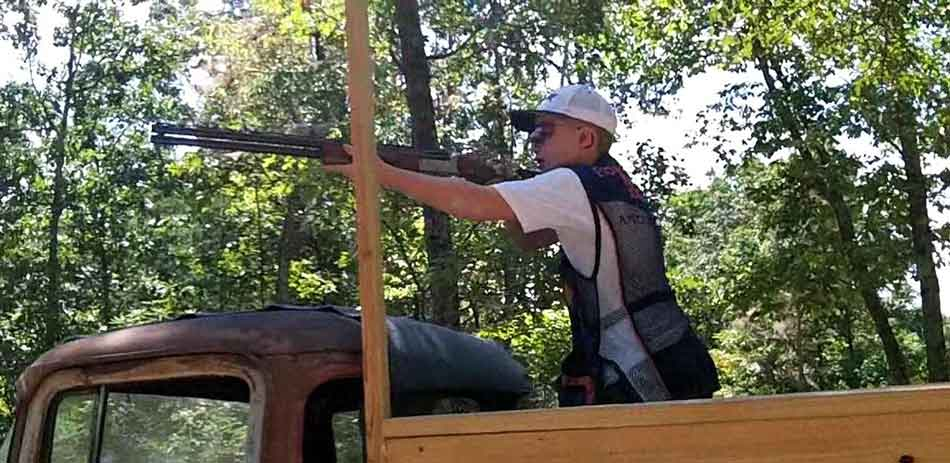 a man clay sport shooting with a shotgun