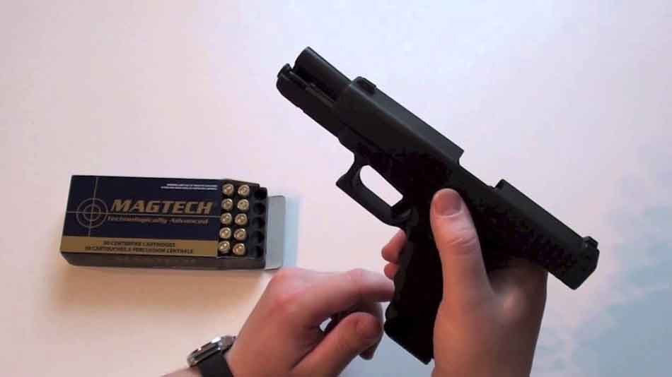 an unloaded glock with magazine and bullets in hand