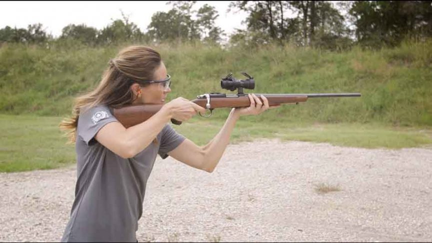 a woman holding and aiming a 22lr rifle