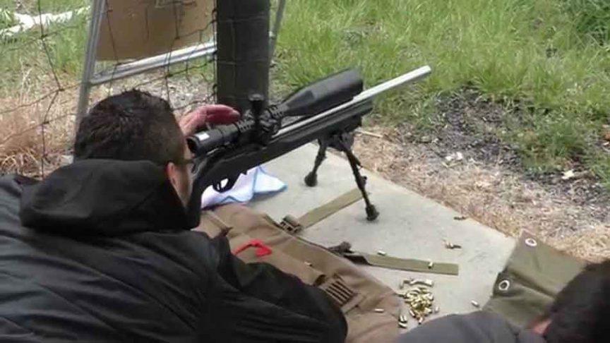 a man firing a 22lr rifle on a range
