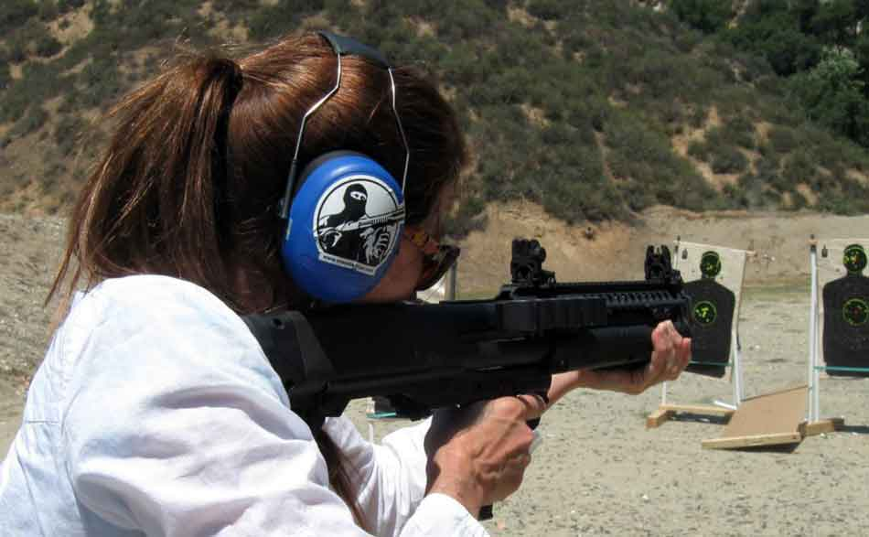 The Kel-Tec KSG-25 shotgun being fired by a woman