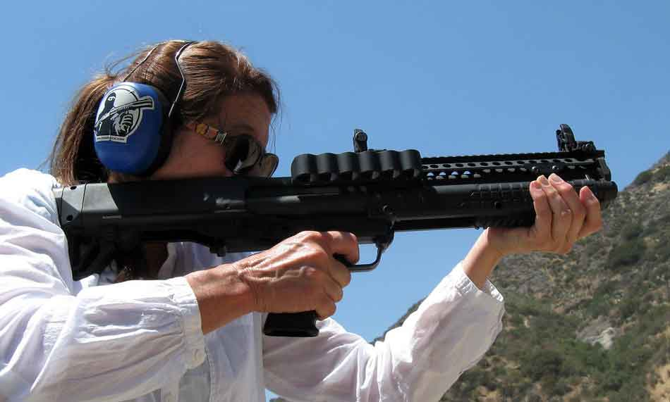 The Kel-Tec KSG-25 shotgun side view being fired by a woman