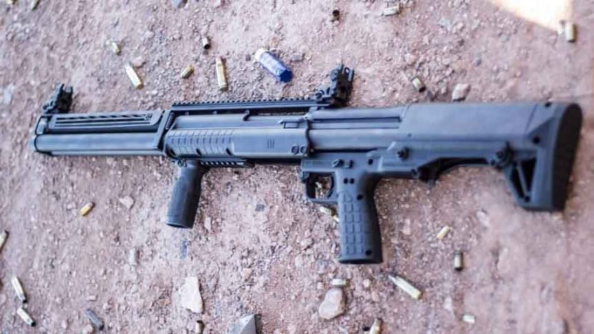 The Kel-Tec KSG-25 shotgun lying on the ground with rounds