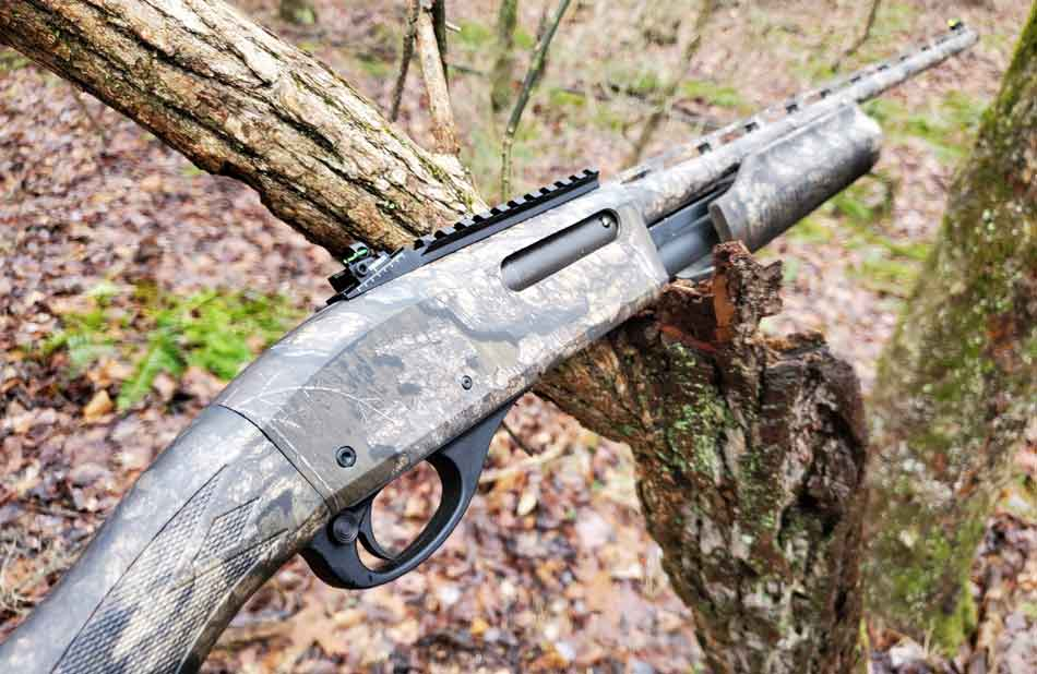 A patterned Remington 870 leaning on a tree