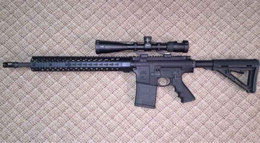 an AR-10 with a Nikon scope on a textured pattern