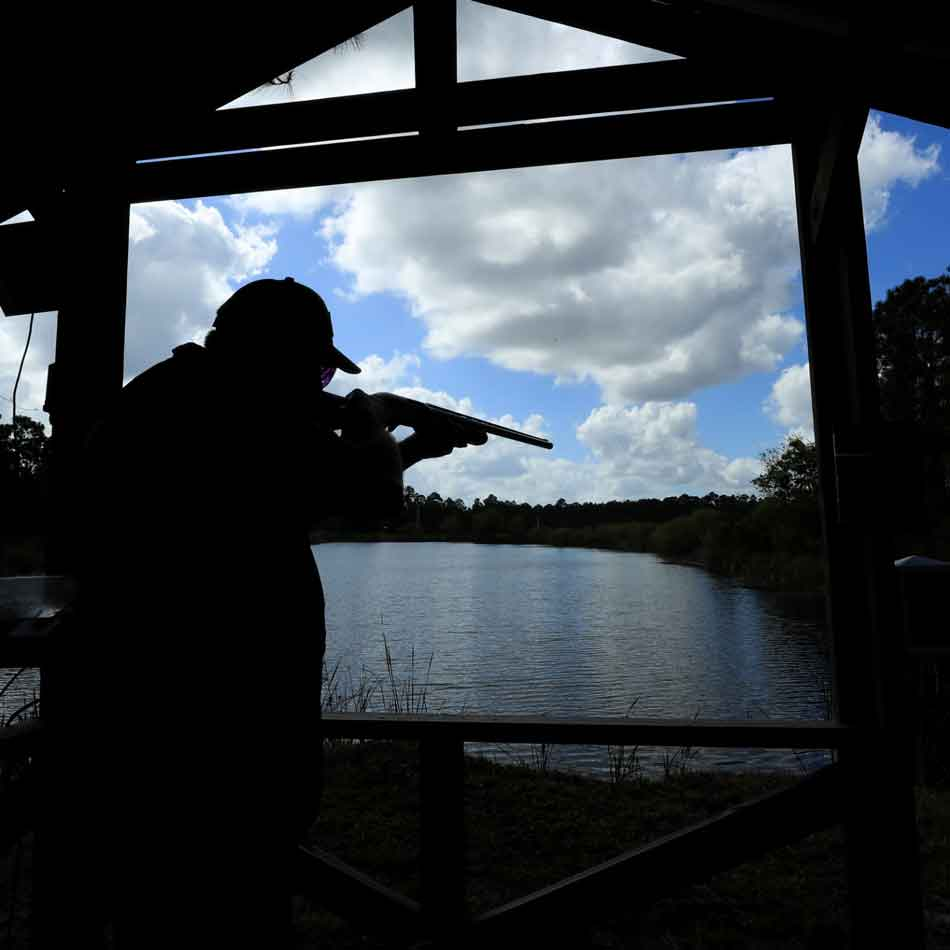 a man pointing a shotgun over a lake