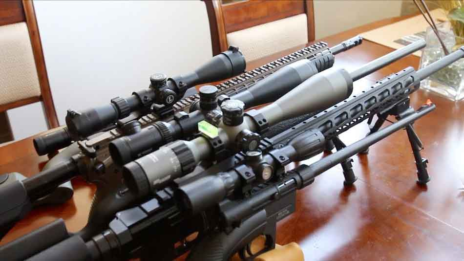 a selection of scopes of several rifles