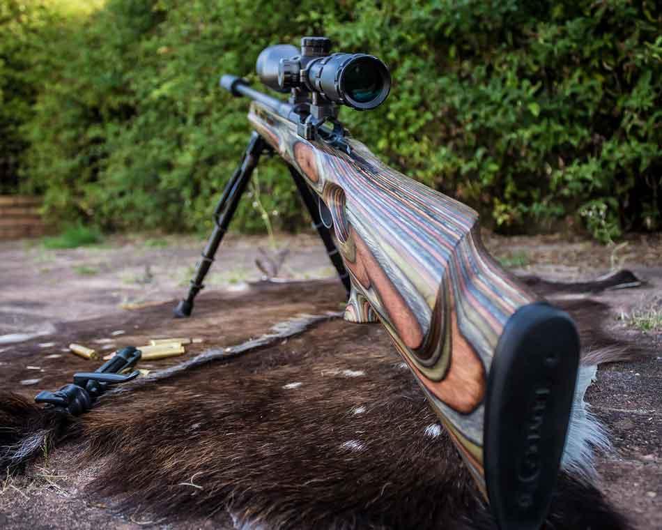 a rifle and scope on a pelt
