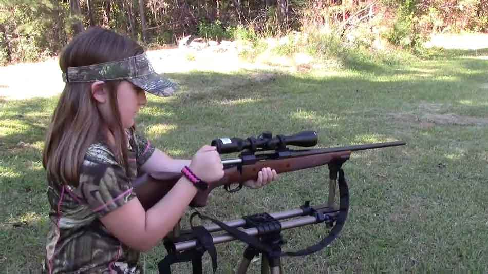 a young girl with a bolt action rifle