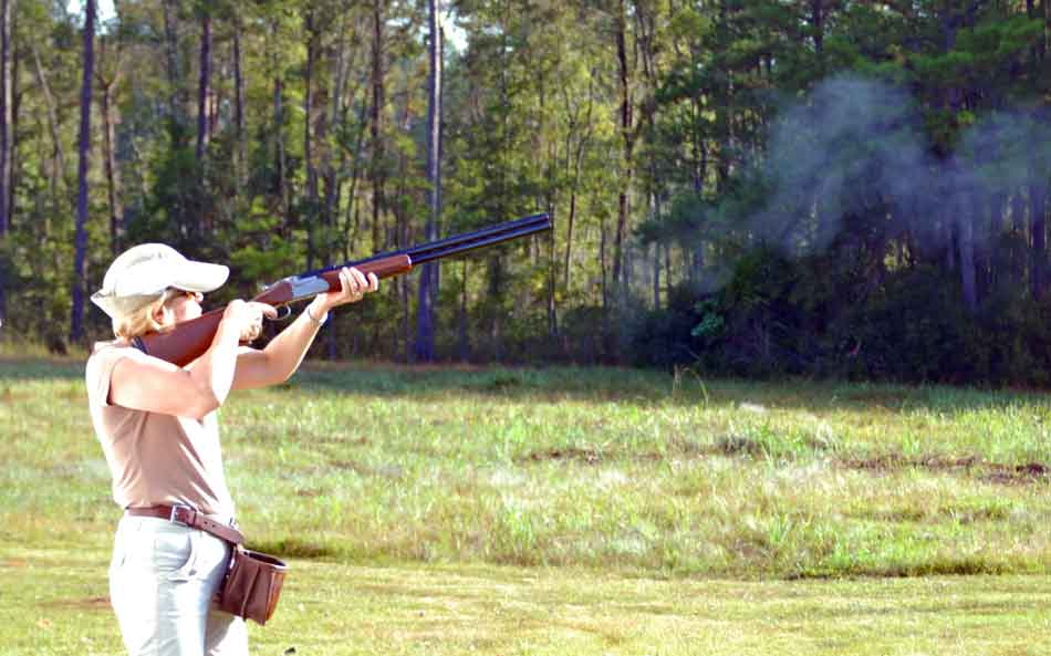 a female skeet shooter at a station with a 12 gauge firing