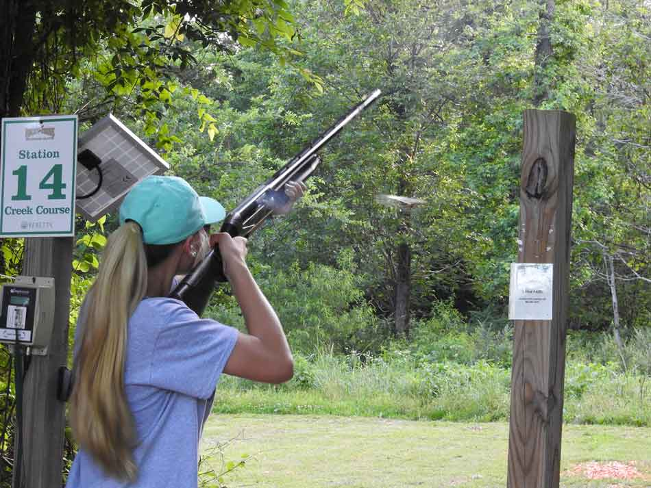 a lady with a semi auto shotgun at a stand for sporting clays