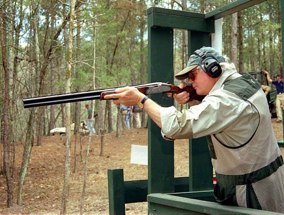 a man with an over and under shotgun at a stand for sporting clays