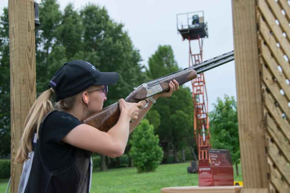 a lady with an over and under shotgun at a stand for sporting clays