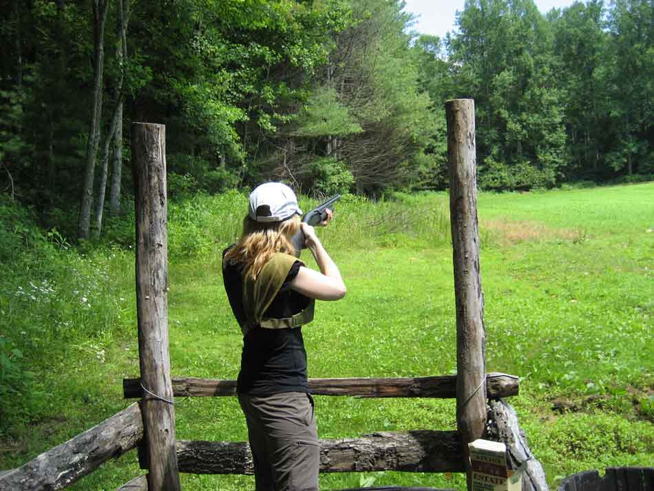a lady with a shotgun at a stand for sporting clays