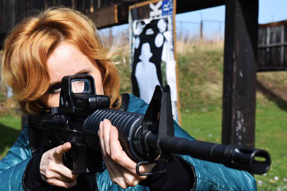 a woman firing a 556 AR-15
