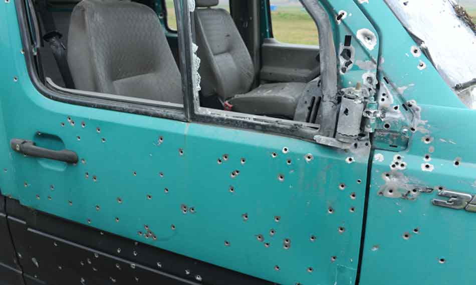 a blue van with many bullet holes in the door