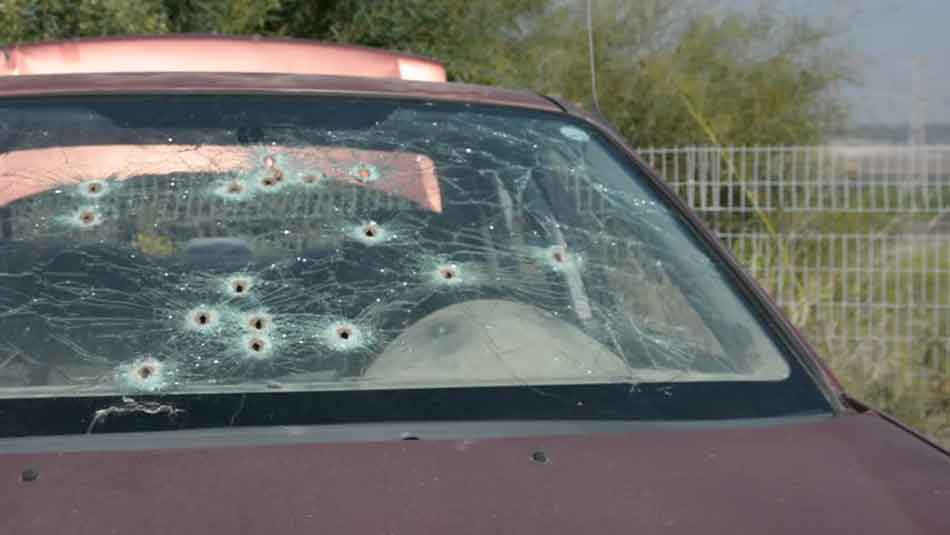 a red car with many bullet holes in the rear window