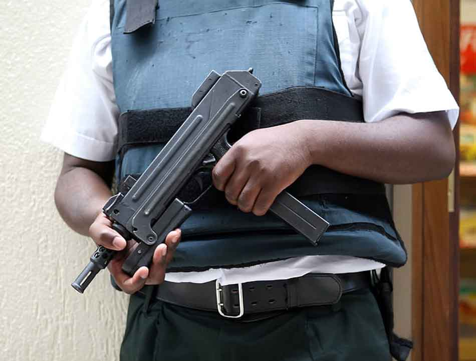 a man wearing body armor and carrying an uzi