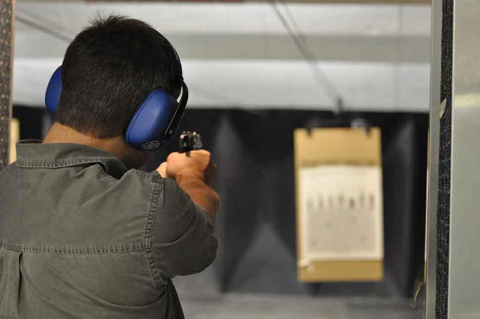 a man firing a pistol on a firing range