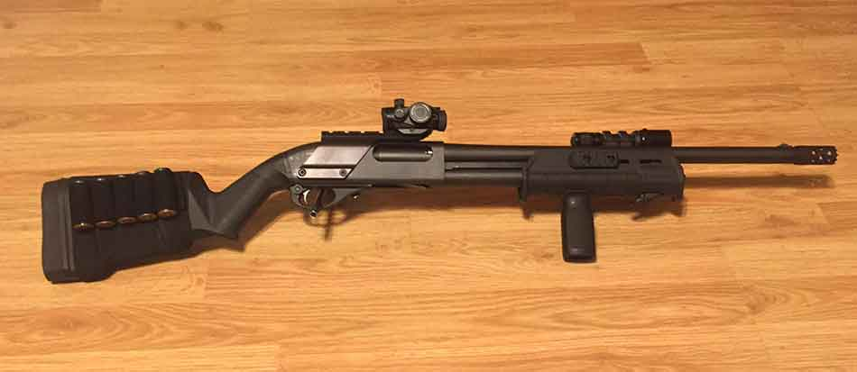 A shotgun with a red dot sight full view