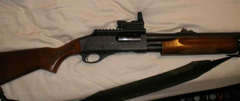 A shotgun with a red dot sight on it side view
