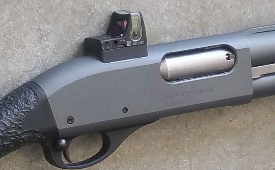 A shotgun with a red dot sight on it close up